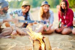 Burning wood on background of restful friends