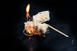 burning wood wool barbecue lighter on a black metal bowl, copy space, selected focus