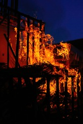 Burning wooden building at night, close up view.