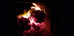 Burning wooden logs in a square opening of the oven, against a black background of the night (abstraction).