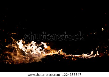 Burning woods with firesparks, flame and smoke. Strange weird odd elemental fiery figures on black background. Coal and ash. Abstract shapes at night. Bonfire outdoor on nature. Strenght of element #1224353347