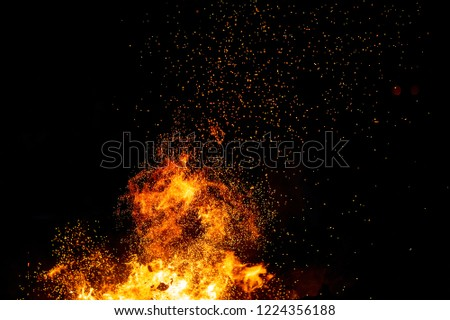 Burning woods with firesparks, flame and smoke. Strange weird odd elemental fiery figures on black background. Coal and ash. Abstract shapes at night. Bonfire outdoor on nature. Strenght of element #1224356188