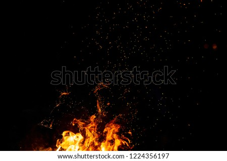 Burning woods with firesparks, flame and smoke. Strange weird odd elemental fiery figures on black background. Coal and ash. Abstract shapes at night. Bonfire outdoor on nature. Strenght of element #1224356197