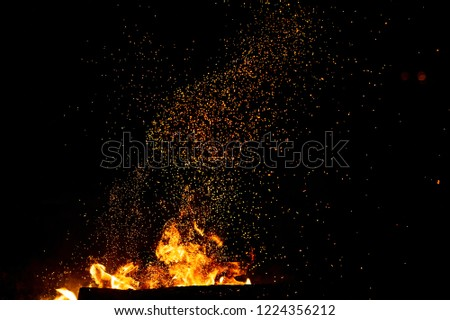 Burning woods with firesparks, flame and smoke. Strange weird odd elemental fiery figures on black background. Coal and ash. Abstract shapes at night. Bonfire outdoor on nature. Strenght of element #1224356212