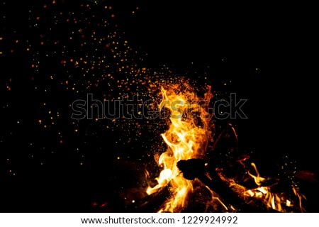 Burning woods with firesparks, flame and smoke. Strange weird odd elemental fiery figures on black background. Coal and ash. Abstract shapes at night. Bonfire outdoor on nature. Strenght of element #1229924992