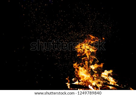 Burning woods with firesparks, flame and smoke. Strange weird odd elemental fiery figures on black background. Coal and ash. Abstract shapes at night. Bonfire outdoor on nature. Strenght of element