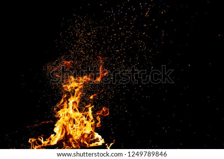 Burning woods with firesparks, flame and smoke. Strange weird odd elemental fiery figures on black background. Coal and ash. Abstract shapes at night. Bonfire outdoor on nature. Strenght of element #1249789846