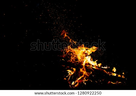 Burning woods with firesparks, flame and smoke. Strange weird odd elemental fiery figures on black background. Coal and ash. Abstract shapes at night. Bonfire outdoor on nature. Strenght of element #1280922250