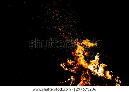 Burning woods with firesparks, flame and smoke. Strange weird odd elemental fiery figures on black background. Coal and ash. Abstract shapes at night. Bonfire outdoor on nature. Strenght of element #1297673206