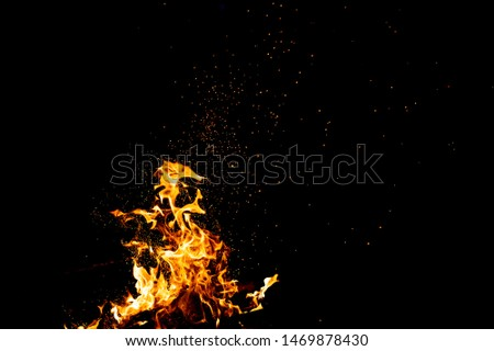 Burning woods with firesparks, flame and smoke. Strange weird odd elemental fiery figures on black background. Coal and ash. Abstract shapes at night. Bonfire outdoor on nature. Strenght of element #1469878430
