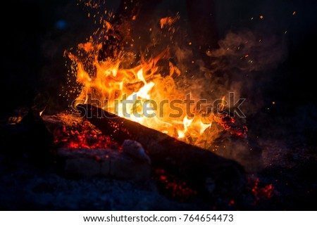 Burning woods with firesparks, flame and smoke. Strange weird odd elemental fiery figures on black background. Coal and ash. Abstract shapes at night. Bonfire outdoor on nature. Strenght of element #764654473