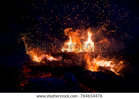 Burning woods with firesparks, flame and smoke. Strange weird odd elemental fiery figures on black background. Coal and ash. Abstract shapes at night. Bonfire outdoor on nature. Strenght of element #764654476