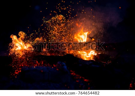 Burning woods with firesparks, flame and smoke. Strange weird odd elemental fiery figures on black background. Coal and ash. Abstract shapes at night. Bonfire outdoor on nature. Strenght of element #764654482