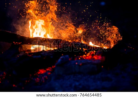 Burning woods with firesparks, flame and smoke. Strange weird odd elemental fiery figures on black background. Coal and ash. Abstract shapes at night. Bonfire outdoor on nature. Strenght of element #764654485