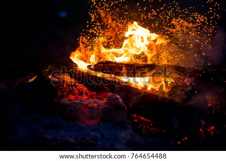 Burning woods with firesparks, flame and smoke. Strange weird odd elemental fiery figures on black background. Coal and ash. Abstract shapes at night. Bonfire outdoor on nature. Strenght of element #764654488