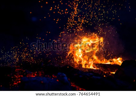 Burning woods with firesparks, flame and smoke. Strange weird odd elemental fiery figures on black background. Coal and ash. Abstract shapes at night. Bonfire outdoor on nature. Strenght of element #764654491