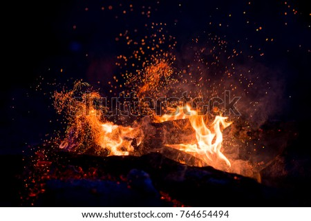 Burning woods with firesparks, flame and smoke. Strange weird odd elemental fiery figures on black background. Coal and ash. Abstract shapes at night. Bonfire outdoor on nature. Strenght of element #764654494