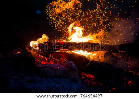 Burning woods with firesparks, flame and smoke. Strange weird odd elemental fiery figures on black background. Coal and ash. Abstract shapes at night. Bonfire outdoor on nature. Strenght of element #764654497