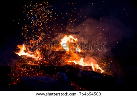 Burning woods with firesparks, flame and smoke. Strange weird odd elemental fiery figures on black background. Coal and ash. Abstract shapes at night. Bonfire outdoor on nature. Strenght of element #764654500