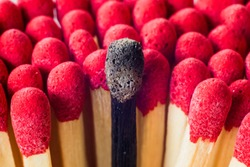 Burnout syndrome, stress, exhaustion and work-life balance concept.  Close-up of a single burnt match in a group of matches.