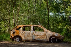 Burnt and abandoned car found wrecked, windowless and undriveable In the forest among the trees Australia