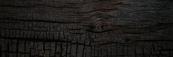 Burnt black wooden board backdrop. Burned scratched hardwood surface, banner. BBQ background.