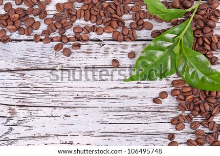 burnt brown arabica coffee beans and green leafs on a white wooden board, background