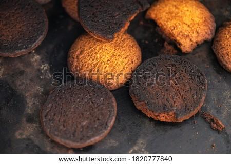 Photo of  Burnt cookies. Burnt, burnt oatmeal cookies lie on a black baking sheet.
