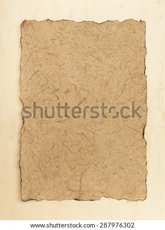 Burnt edges natural texture paper on wood background vertical style