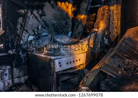 Burnt house interior. Burned kitchen, remains of stove and furniture in black soot. #1267699078