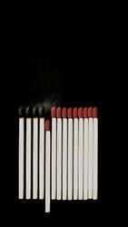 Burnt matches and whole matches on black background. The spread of fire. One whole match isolated to stop fire. Stop destruction concept. Social distance. Pile of match stick. Covid-19. Burnt matches