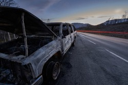 Burnt out car wreck on road