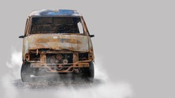 Burnt out delivery van isolated on grey background
