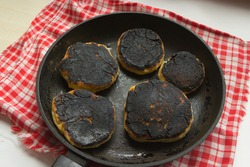 burnt pancakes, cheesecakes, food in a pan. Fried foods are unhealthy. carcinogens in fried foods