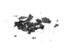 Burnt paper on a white background. The ashes of the paper. Charred paper scraps.
