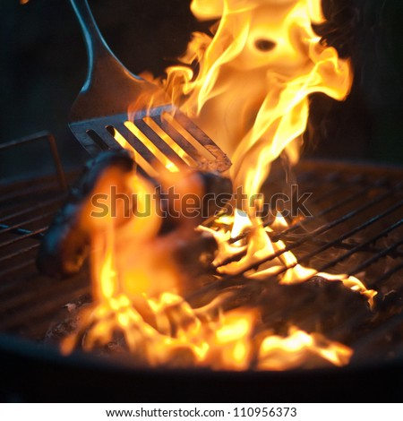 Burnt Sausages being flipped in a BBQ flame
