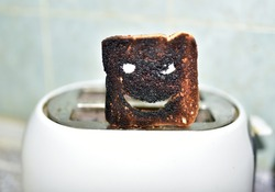 Burnt toast with an angry face expressing the emotion of sadness or sarcasm. Burnt toast bread slices out of a toaster. Сoncept of unsuccessful breakfast preparation before a work day or weekend