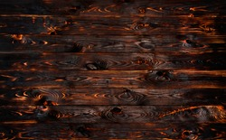 Burnt wooden board, black charcoal wood texture, burned coal barbecue background with copy space, top view