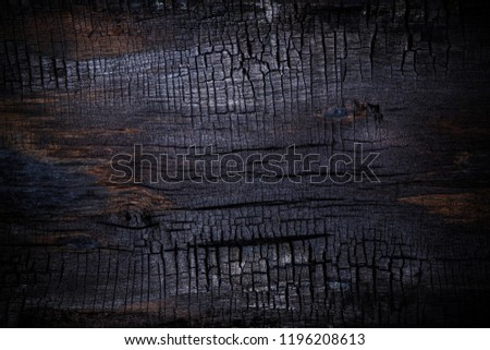 Burnt wooden Board texture. Burned scratched hardwood surface. Smoking wood black plank halloween background