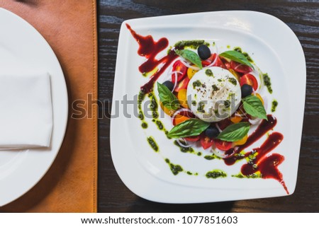 Burrata cheese salad including sliced tomato, onion, grape, basil leaves with pesto and red sauce. #1077851603