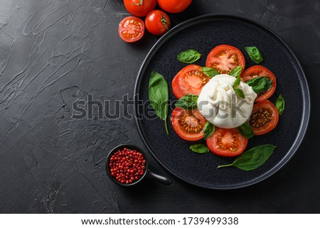 Burrata, Italian fresh cheese made from cream and milk of buffalo or cow. on black plate over black stone surface top view space for text. Stockfoto ©