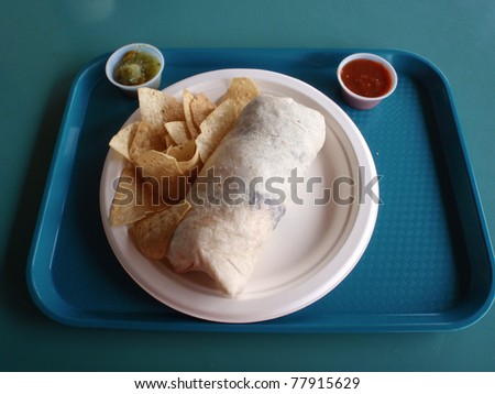 Burrito and Chips on Paper plate with small cups of red and green sauce on blue tray on a blueish-green table.