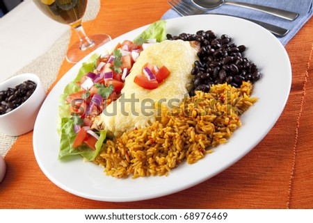 Burrito plate with a side of black beans rice and a fresh salad.