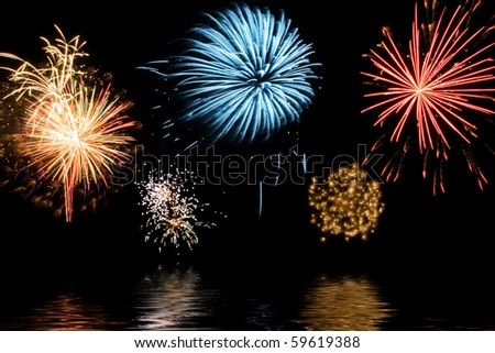 Bursts of colorful fireworks reflecting in water