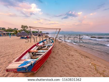 Burundi Bujumbura lake Tanganyika, windy cloudy sky and sand beach at sea lake in East Africa, Burundi sunset with boat from wood. Thatch african roofs on umbrellas