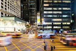 Bus and cars, captured with blurred motion, rush through a major interesection in the Central business and shopping district in Hong Kong at night