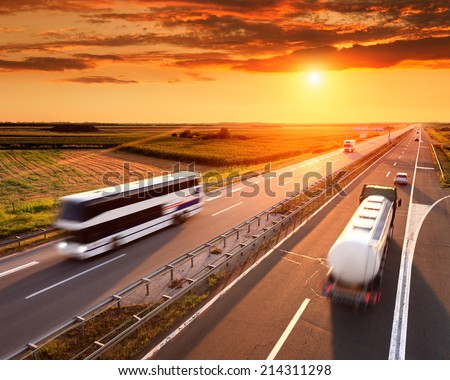 Bus and truck in motion blur on the highway at sunset