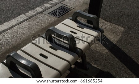 Bus benches in the sunlight and shadows with no one sitting down #661685254