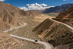 Bus on a desert road high on the Tibetan Plateau near the town of Tsetang in the Tibet Autonomous Region of China.