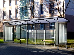 bus shelter and bus stop. glass and aluminum structure in park like setting in day time with green background and appealing polka dot safety glass design and wooden benches and poster display glass